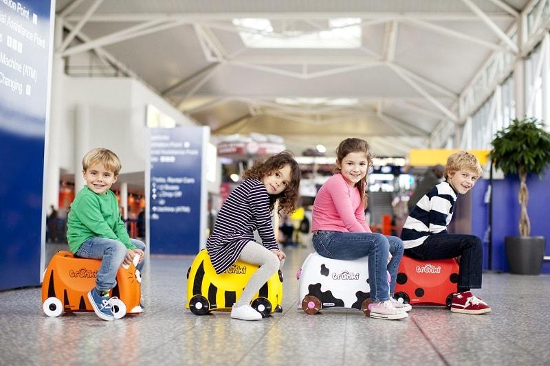 Дети катаются на чемоданах Trunki.